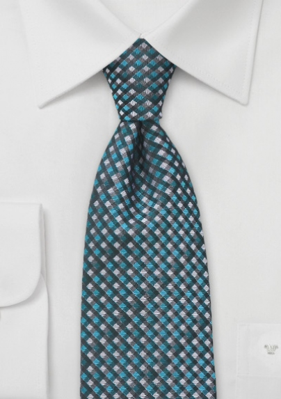 This small scaled plaid patterned tie in available in elegant shades of greys, charcoals and teals. The sleek color palette resonates with a seasonal coolness that pairs handsomely with charcoals. Available at Bows-N-Ties.com. Retail $24.90