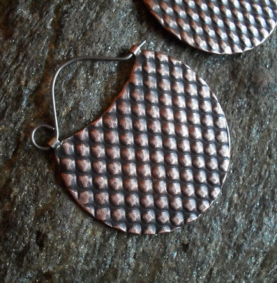 Deeply textured, two-sided earrings in copper, by Lisa Flanders