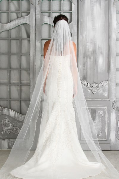 This one-tier pencil edge bridal veil is the perfect complement to a sheath dress and allows the beauty of the gown's back to show through during the wedding ceremony.